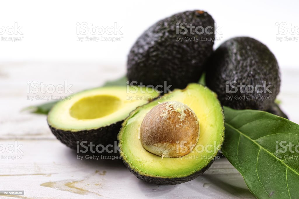 Green ripe avocado with leaves close up stock photo