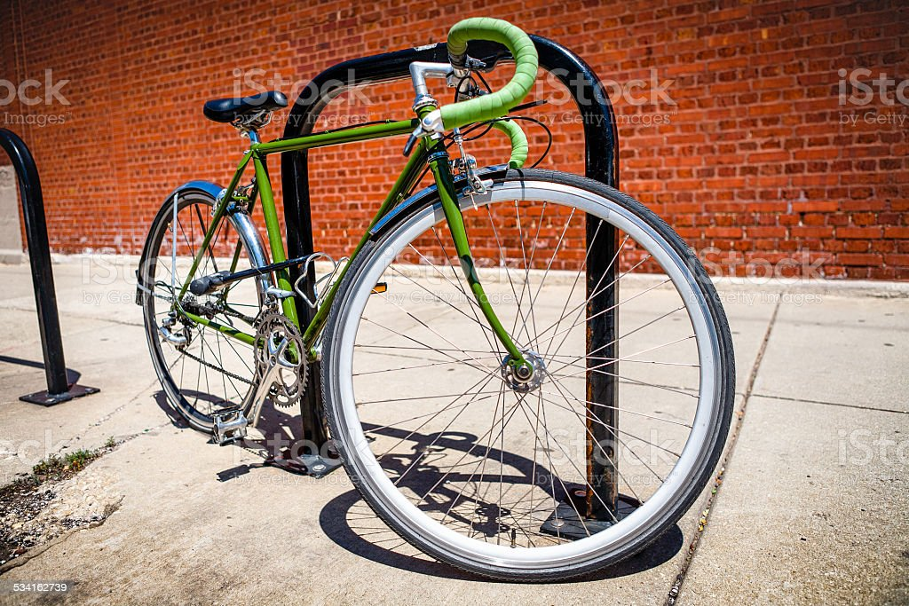 Green Road Bicycle U-Locked To Bike Rack stock photo