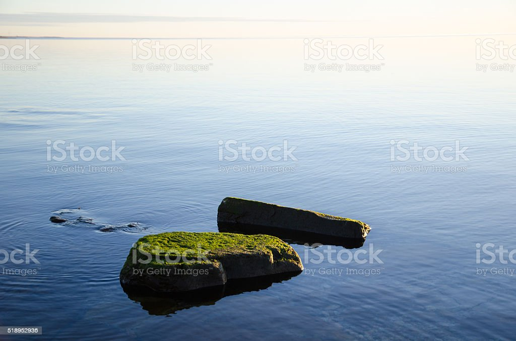 Green rocks in smooth water stock photo
