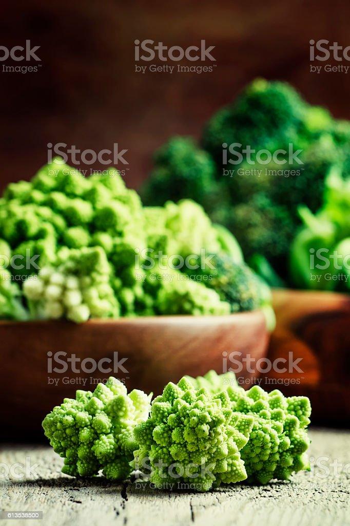Green romanesco cauliflower in a wooden bowl stock photo