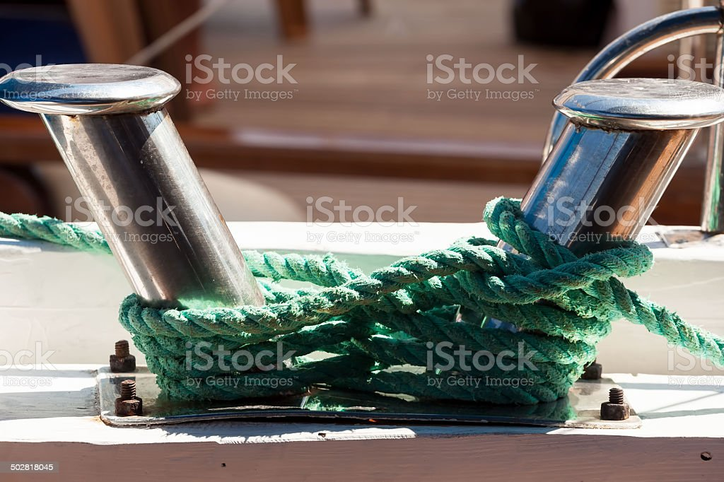 Green rope and damaged Bitt stock photo