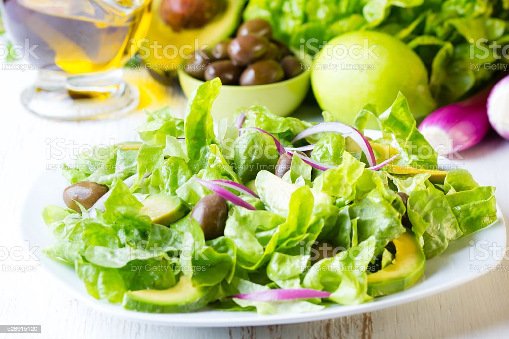 Green salad and ingredients lettuce, avocado, olives, oil, herb onion stock photo