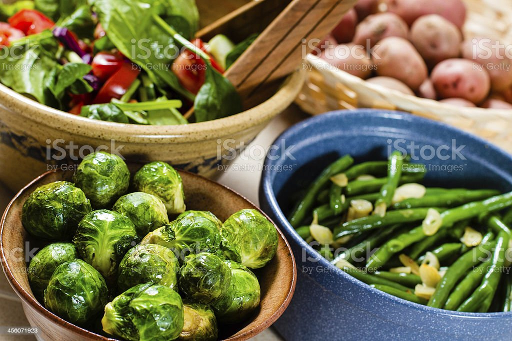 Green salad, cooked brussels sprout, grean beans, potatoes in bowls. royalty-free stock photo