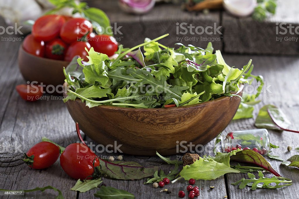 Green salad leaves in a wooden bowl stock photo