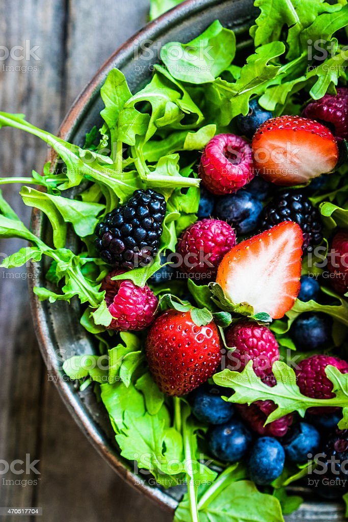 Green salad with arugula and berries stock photo