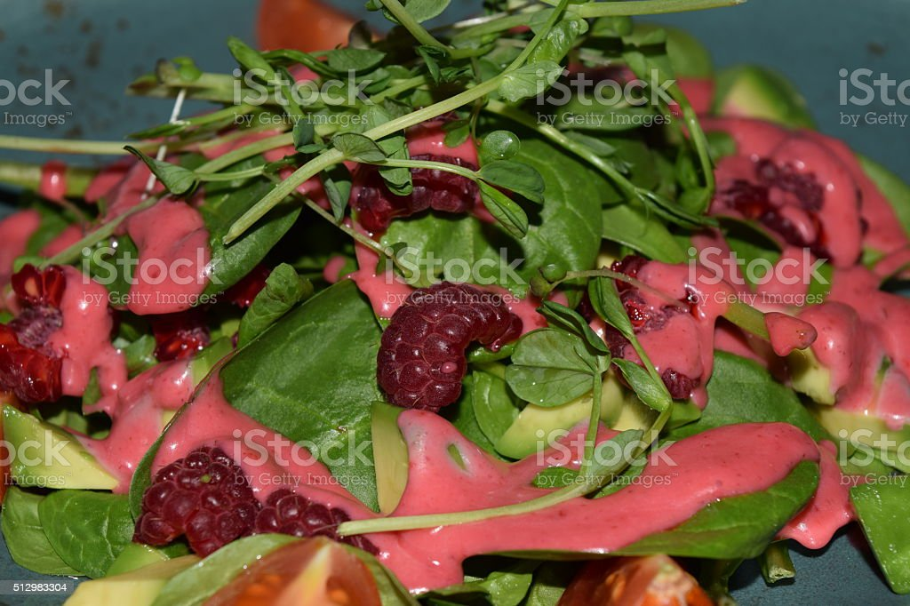 green salad with arugula and raspberry stock photo