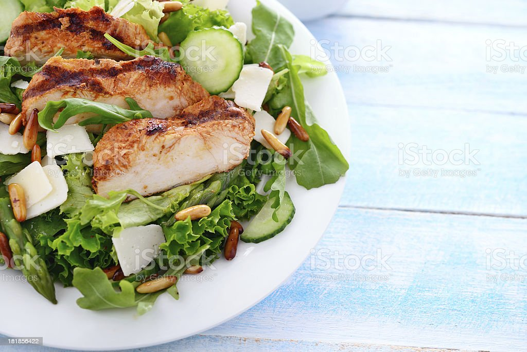 Green salad with grilled chicken slices and rosted pine nuts stock photo