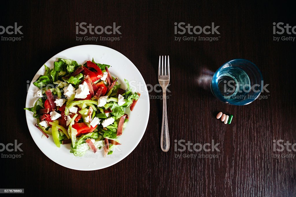 green salad with pills stock photo