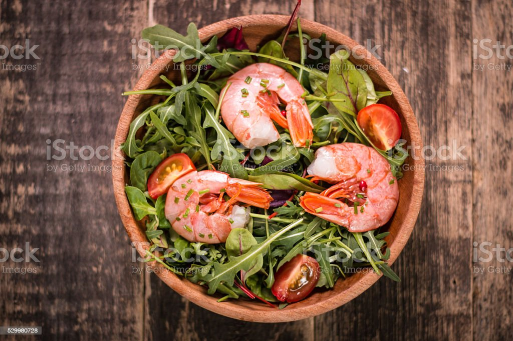 Green salad with shrimps on wooden table.healthy food stock photo