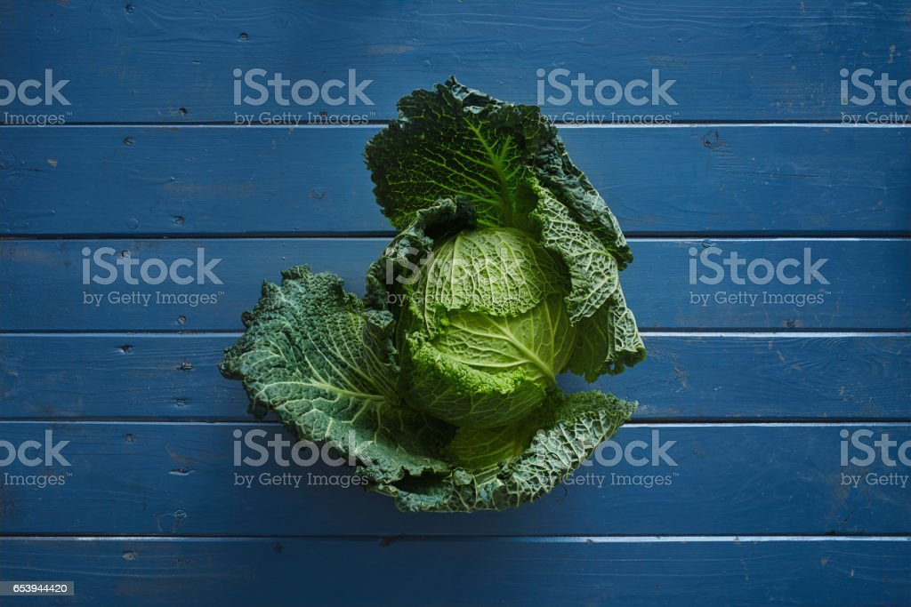 green savoy on blue wooden table stock photo