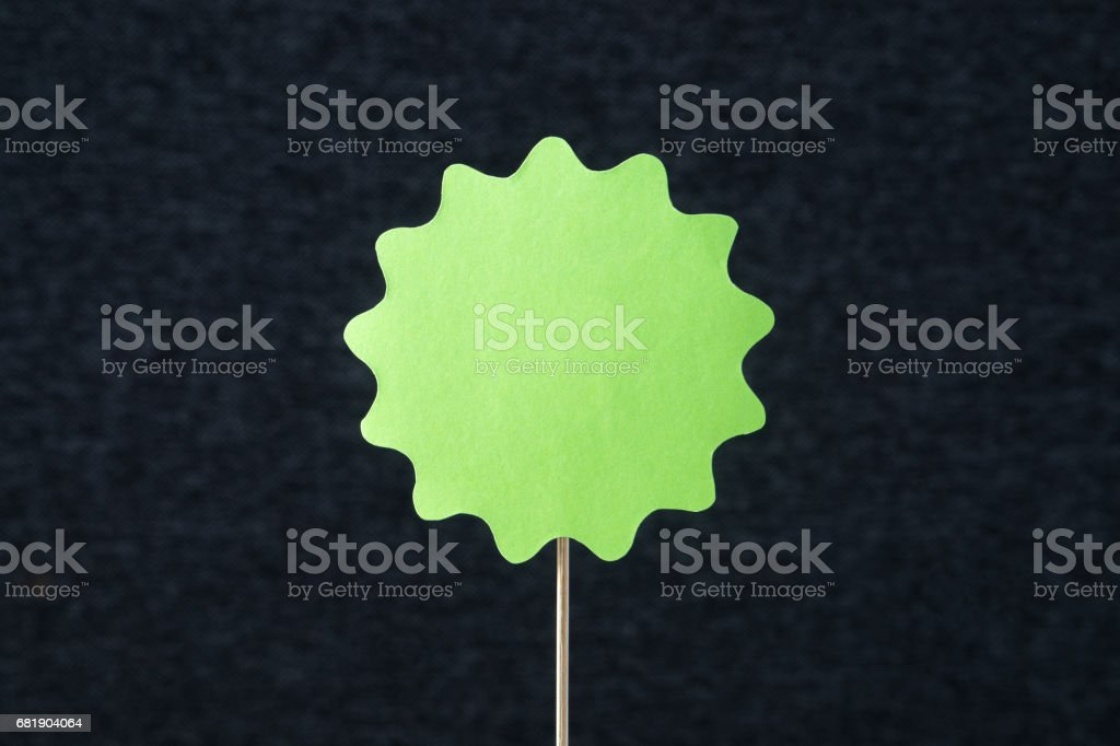 Green shaped circle cut from cardboard on a wooden stick. Template for round paper badge, label, sign, plague or design element with dark gray background and empty blank copy space. Handcraft banner. stock photo