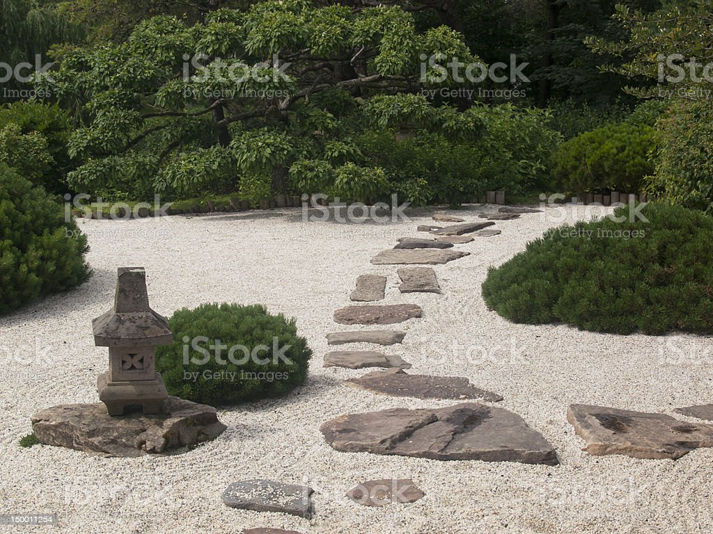Green shrubbery and a stone pathway in a Japanese Zen Garden stock photo