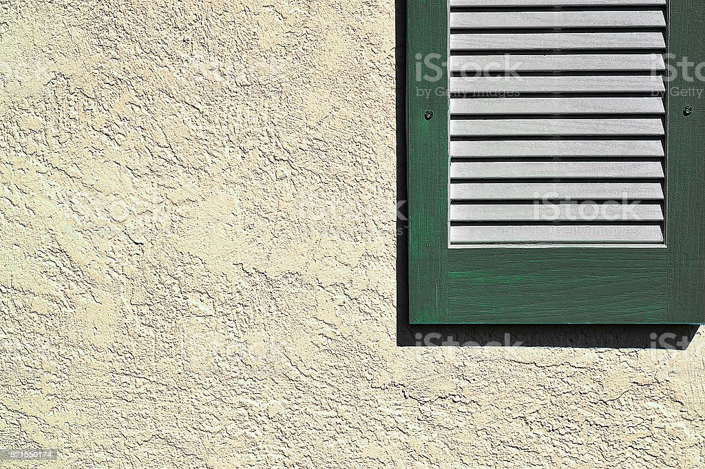 Green shutter on exterior stucco wall stock photo
