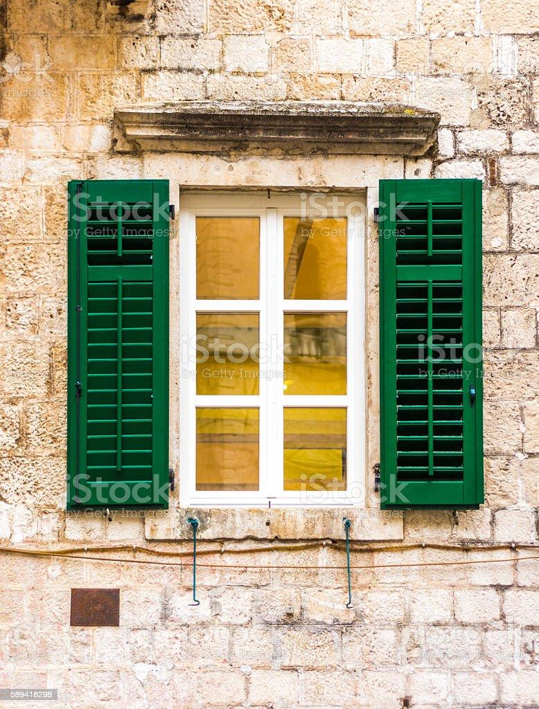 Green shuttered window on stone wall stock photo