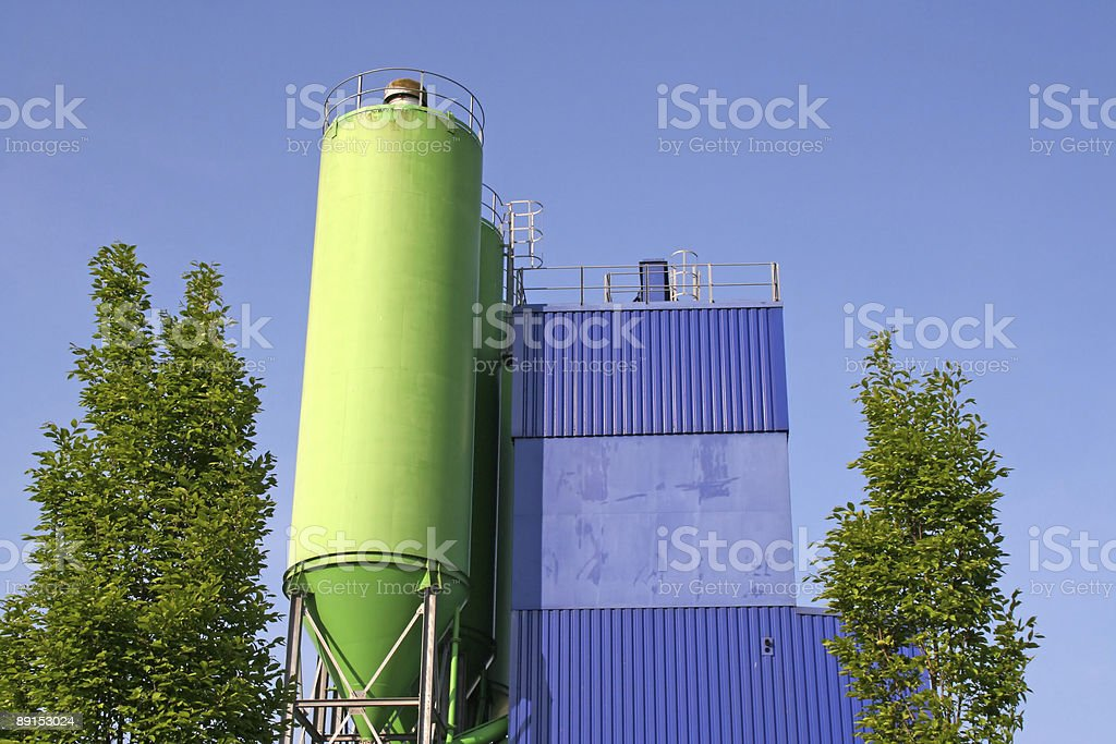 Green silo with blue factory royalty-free stock photo