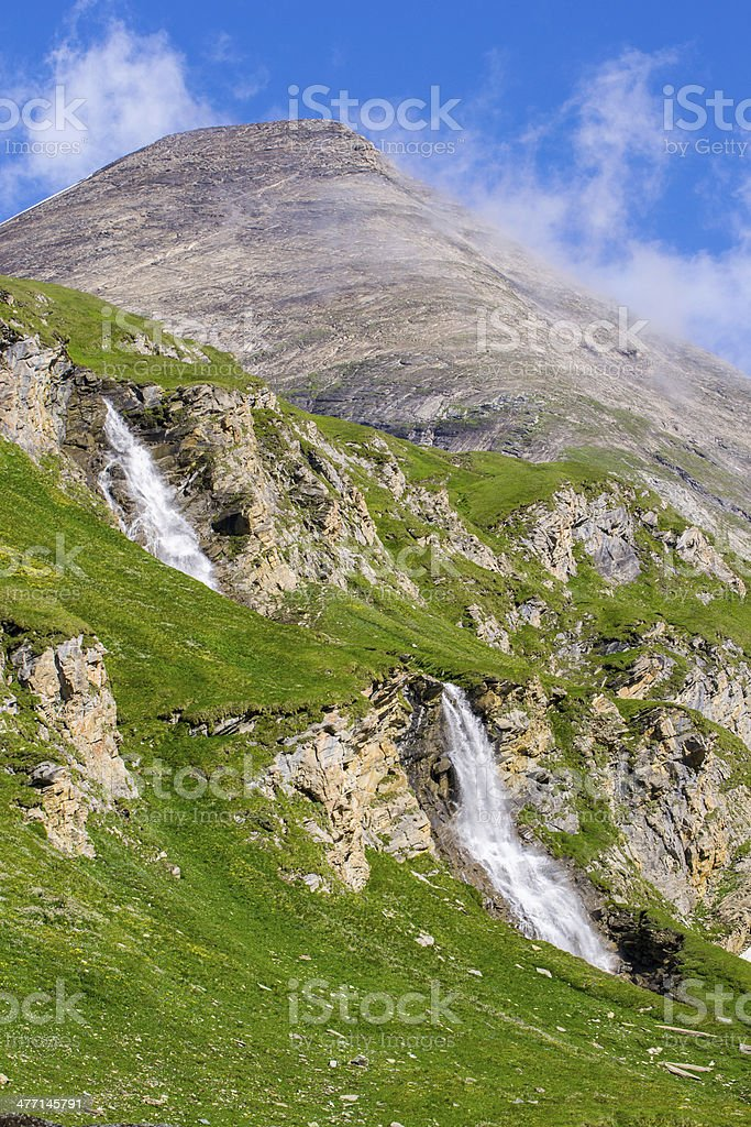 green slopes with two waterfalls and a mountain peak royalty-free stock photo
