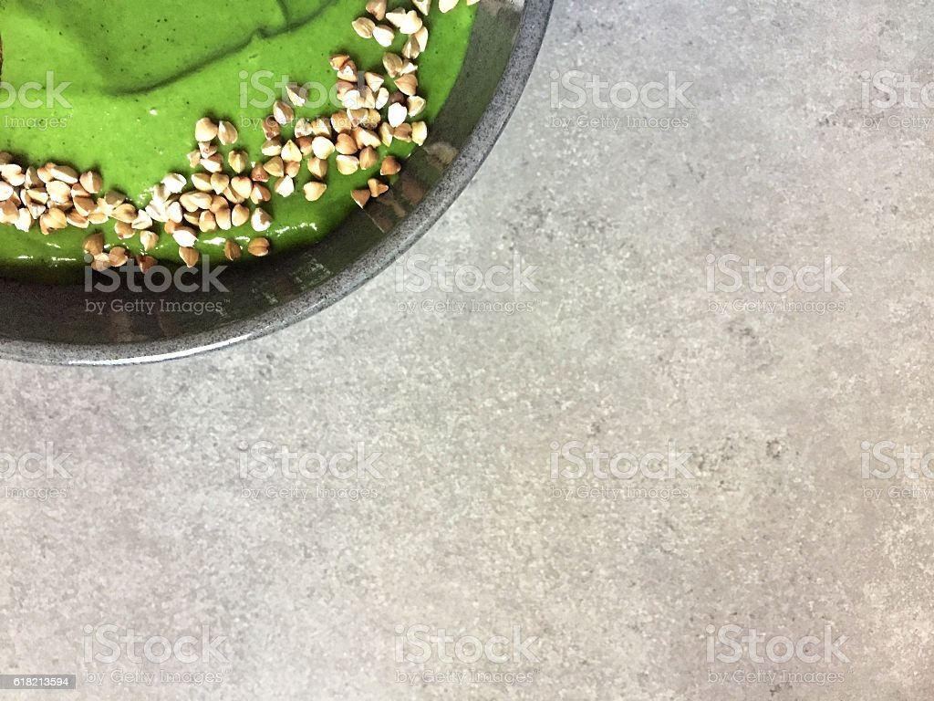 Green smoothie bowl topped with buckwheat, with white space stock photo