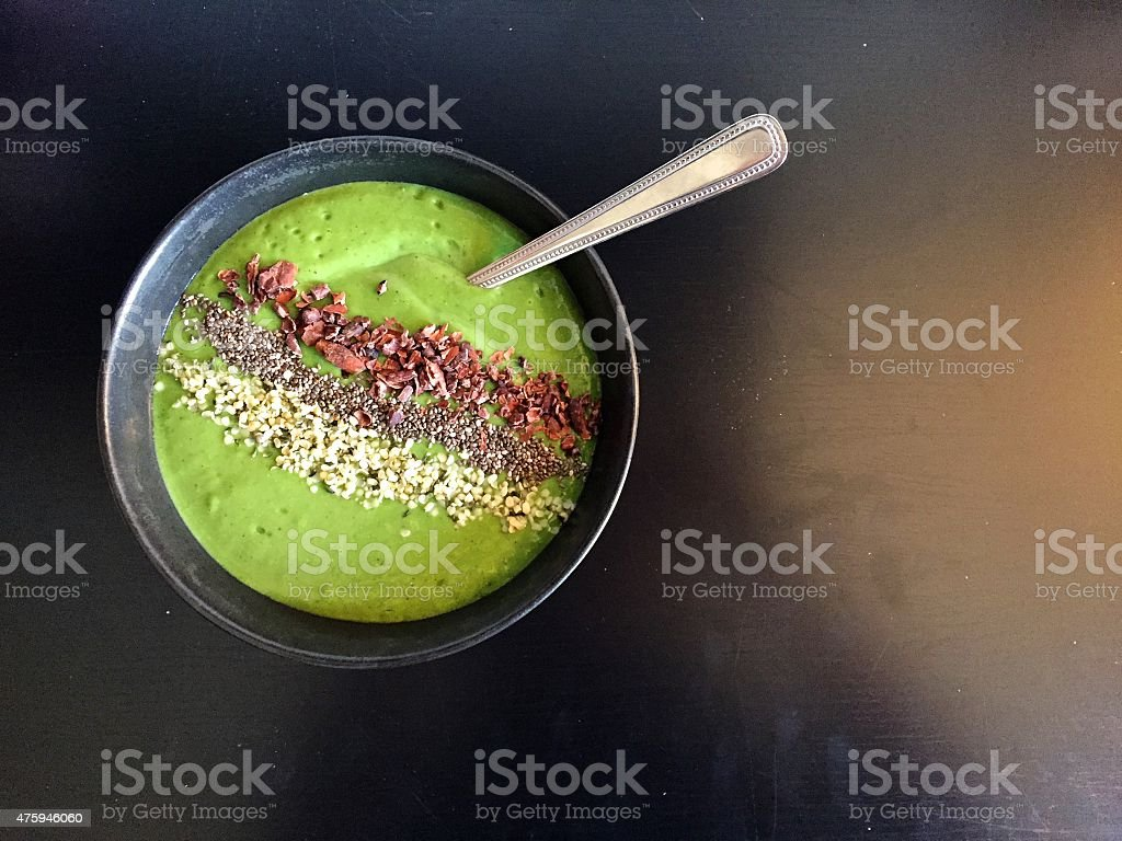 Green smoothie bowl with hempseeds, chia seeds and cacao nibs stock photo