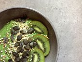 Green smoothie bowl with kiwifruit, pumpkin seeds, buckwheat, hemp seeds