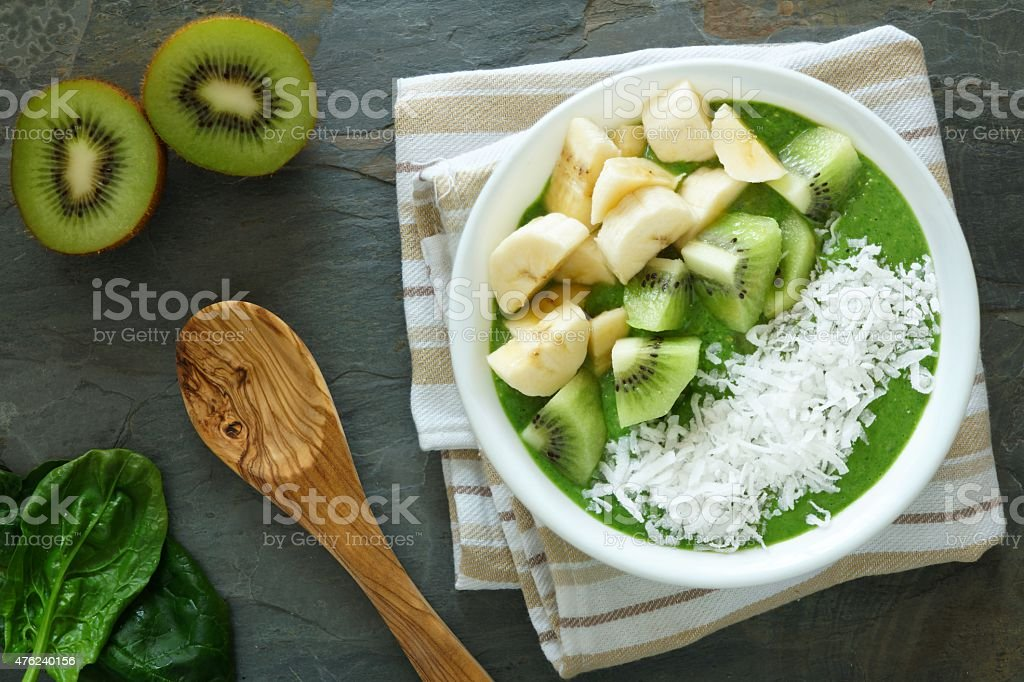 Green smoothie bowl with spinach, kiwi, bananas and coconut stock photo