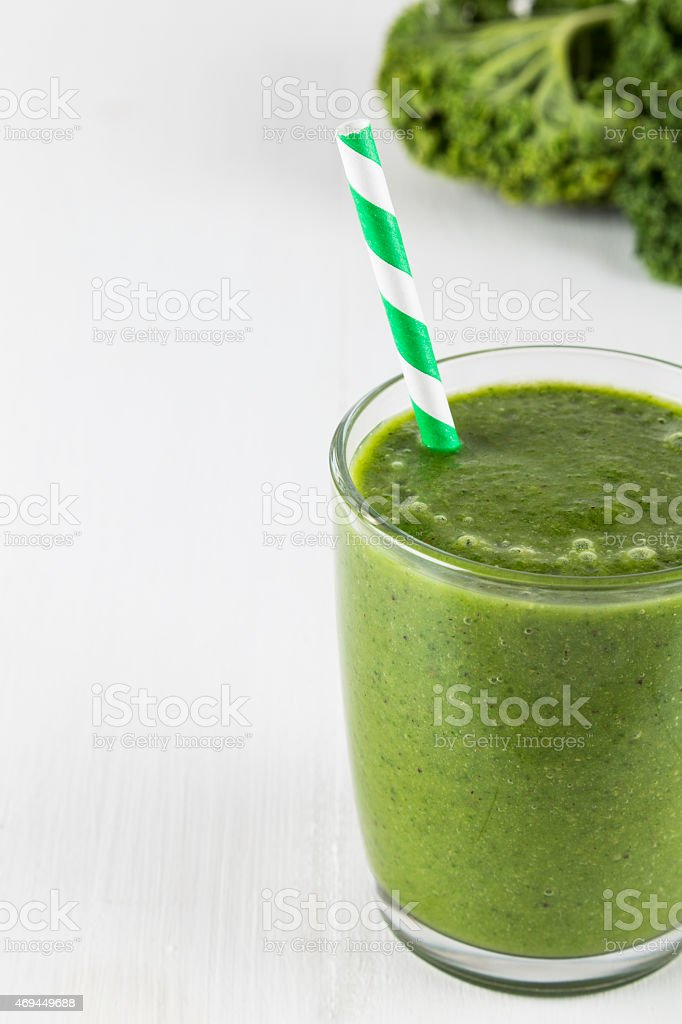 Green smoothie with striped straw stock photo