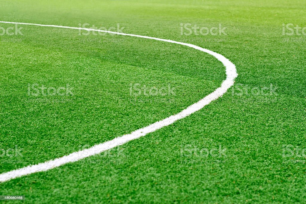 Green soccer field grass with white mark line, soft focus stock photo