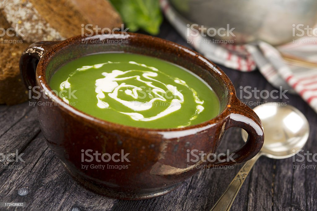 Green soup in a bowl on a rustic table royalty-free stock photo