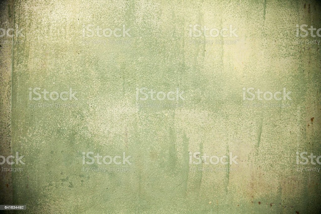 Green spray painted grunge stained wall with rust spots stock photo