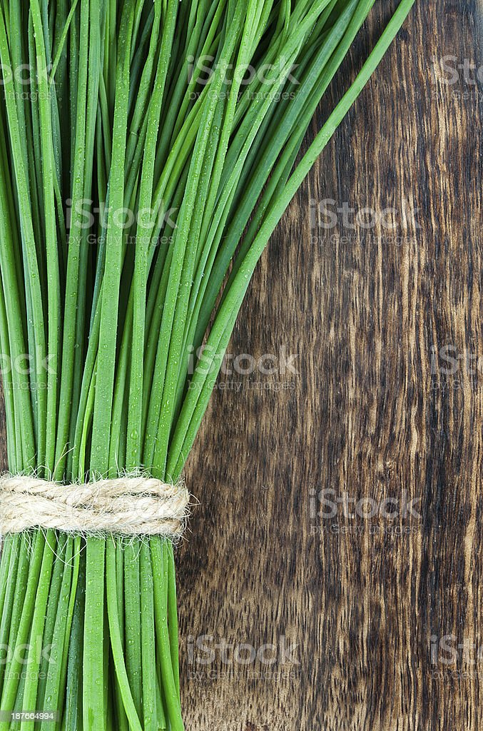 Green spring of onion on brown wooden background stock photo