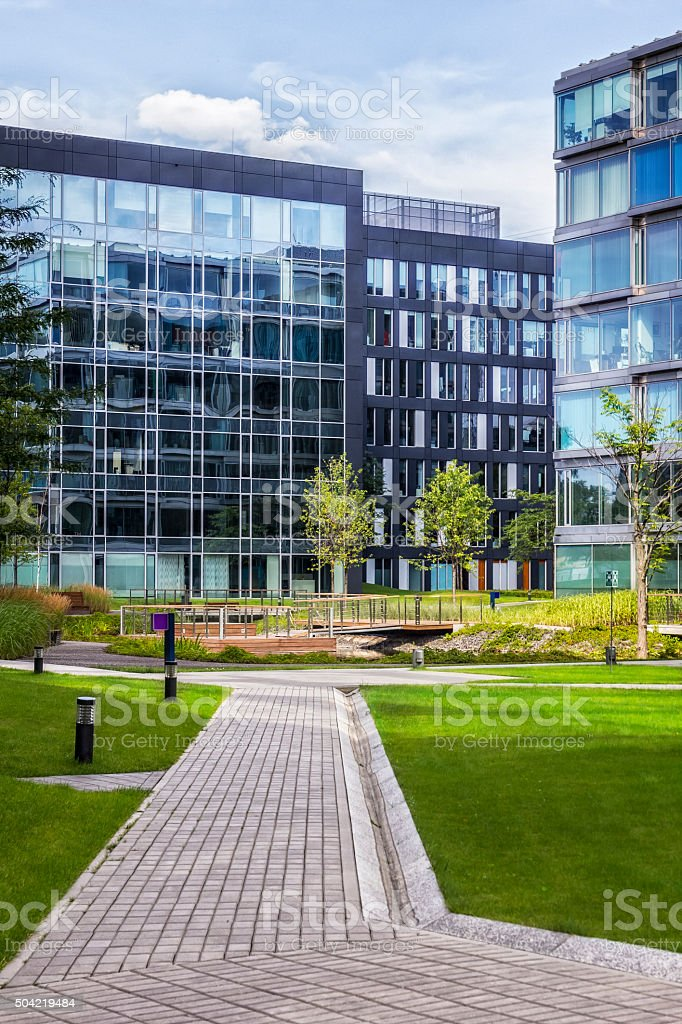 Green square with chairs in front of office buildings stock photo