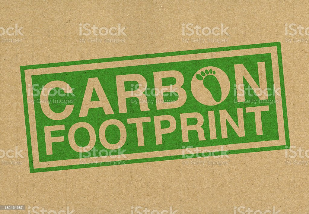Green stamp with CARBON FOOTPRINT on a brown background stock photo