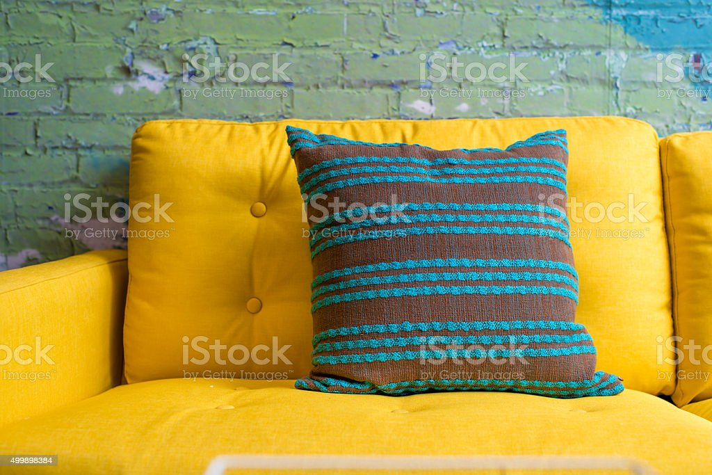 green stripe pillow on vivid yellow sofa stock photo