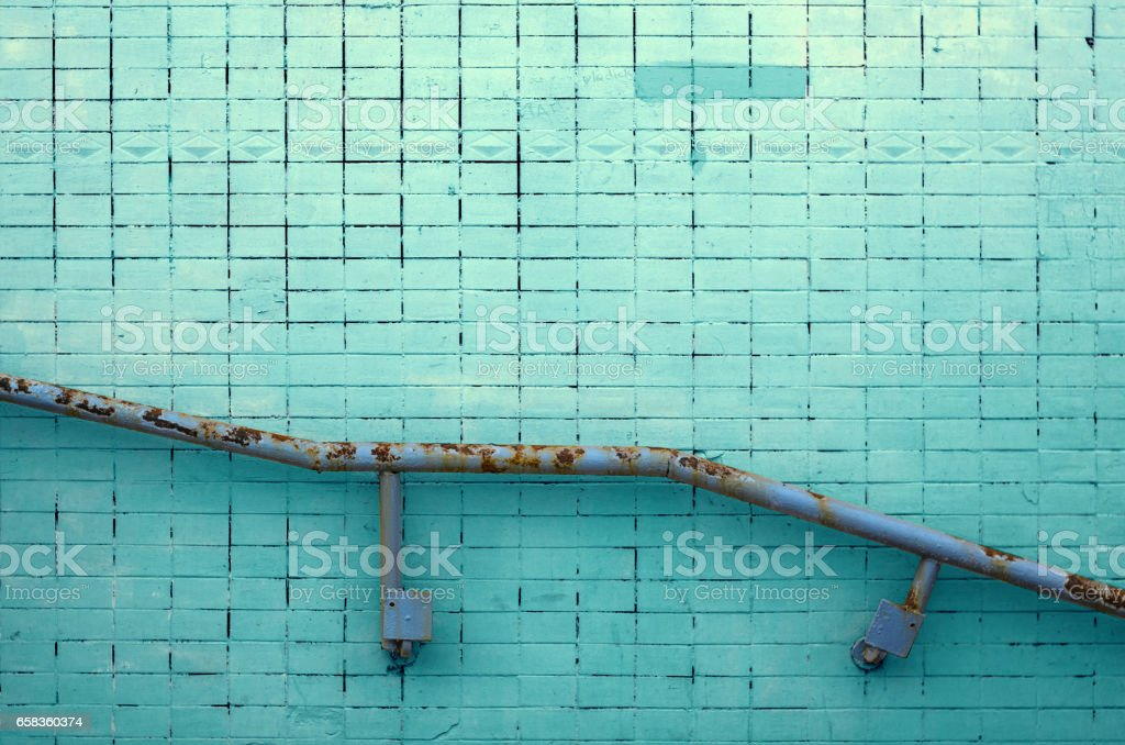 Green stucco wall texture with metal railing for background or copy space. stock photo