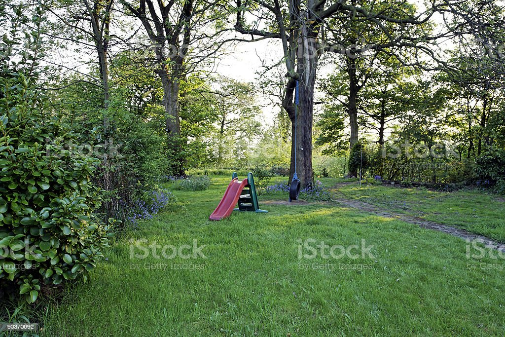 Green Suburban Garden with Trees, Bushes, Rope Swing and Slide royalty-free stock photo