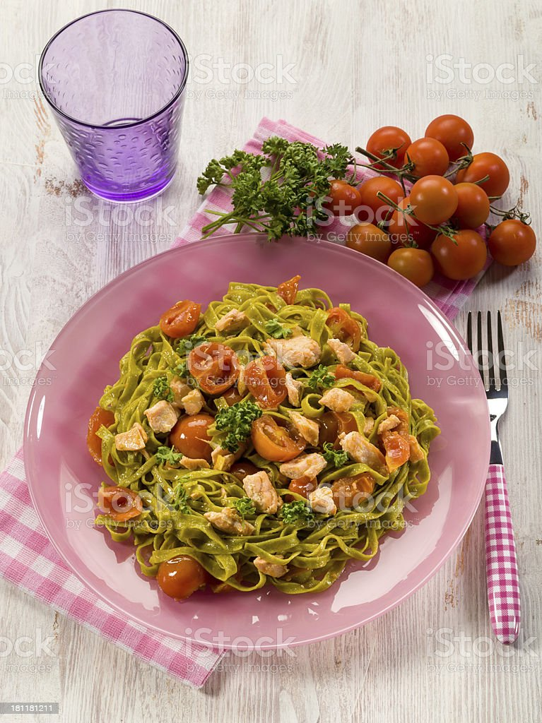 green tagliatelle with fresh salmon and tomatoes royalty-free stock photo