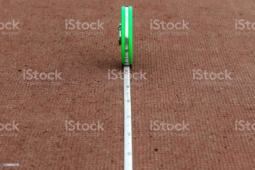 Green tape measure lying on a red running track stadium stock photo