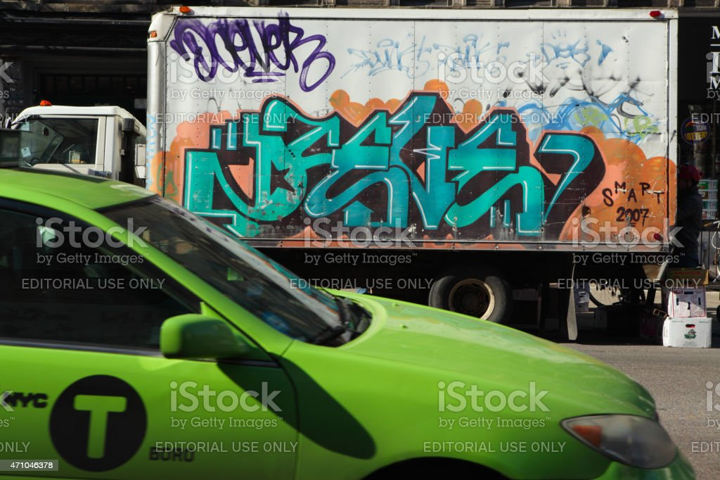 Green taxi cab poasses a graffiti covered van in NYC stock photo