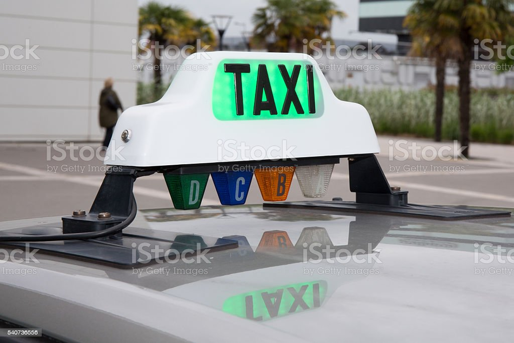 Green taxi sign in France on the car stock photo