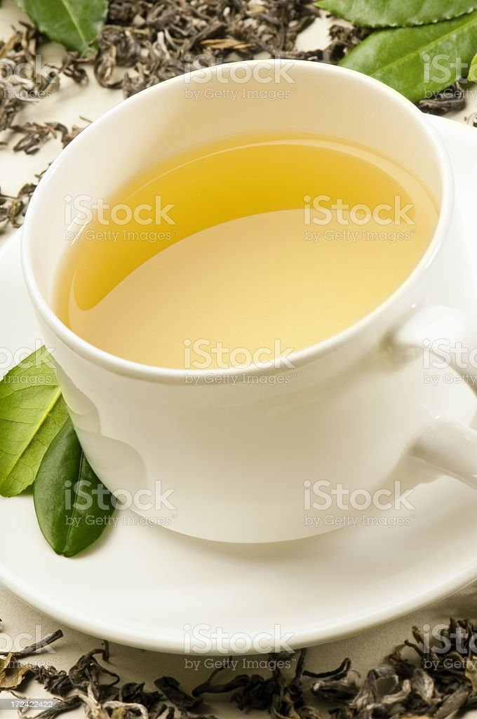 Green tea and tea leaves in white cup and saucer stock photo