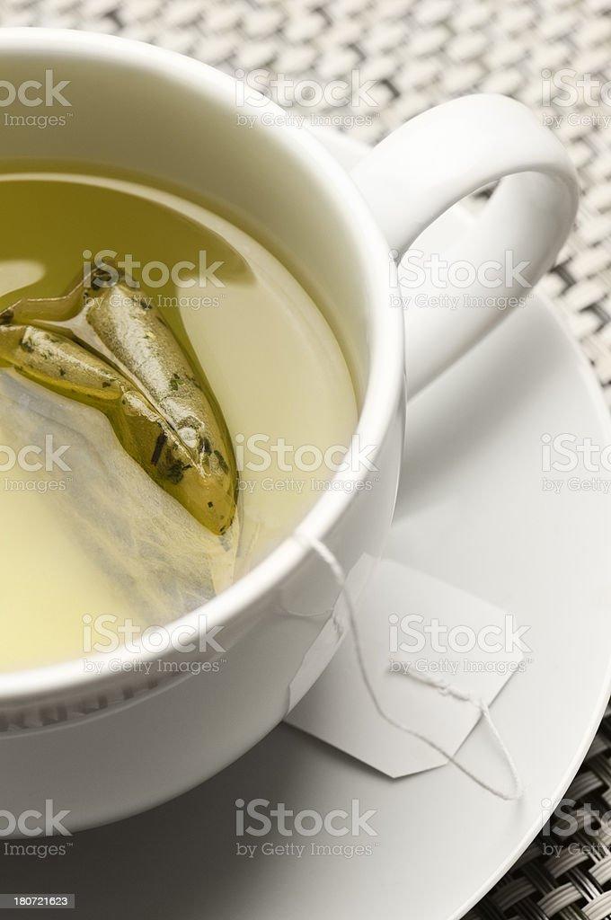 Green tea and teabag in white cup and saucer stock photo