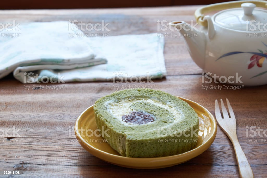 Green tea cake roll and tea pot on wooden background. stock photo