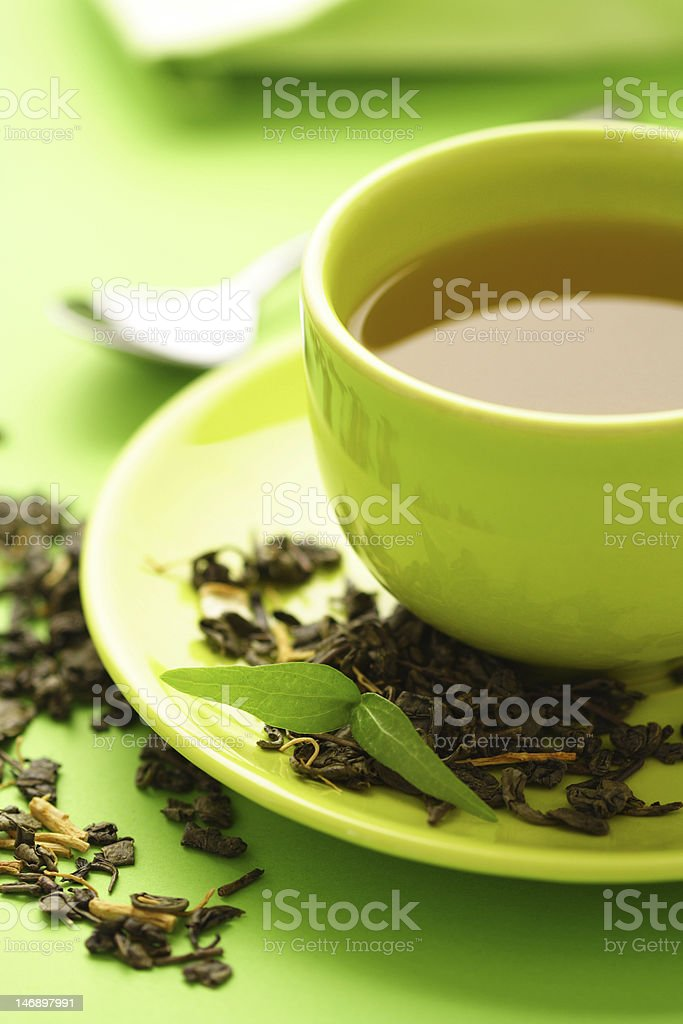 Green tea in a small cup surrounded by tea leaves on a dish royalty-free stock photo
