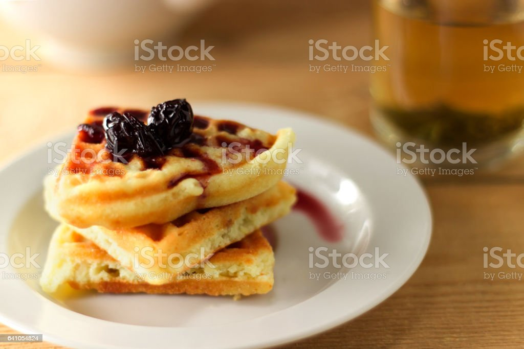 Green tea in a transparent mug with waffle stock photo