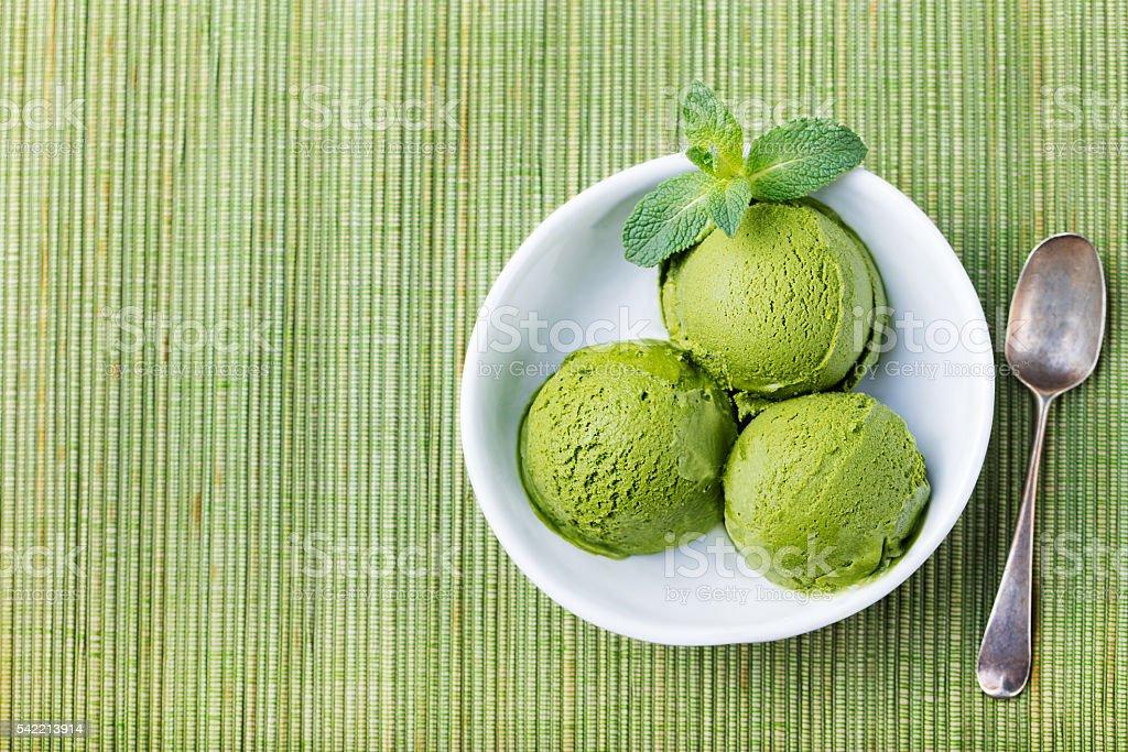Green tea matcha ice cream in white bowl Wooden background stock photo