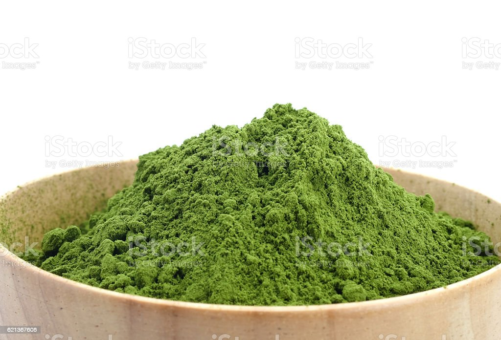 Green tea powder in wood bowl on white background. stock photo