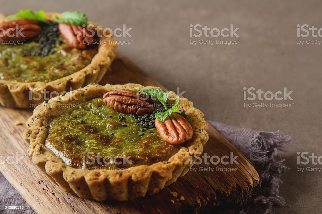 Green tea vegetarian pie match with nuts and mint. Dark backgrou stock photo