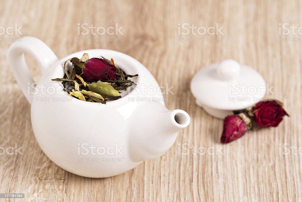 Green tea with fruits, spices, rose petals in a teapot royalty-free stock photo