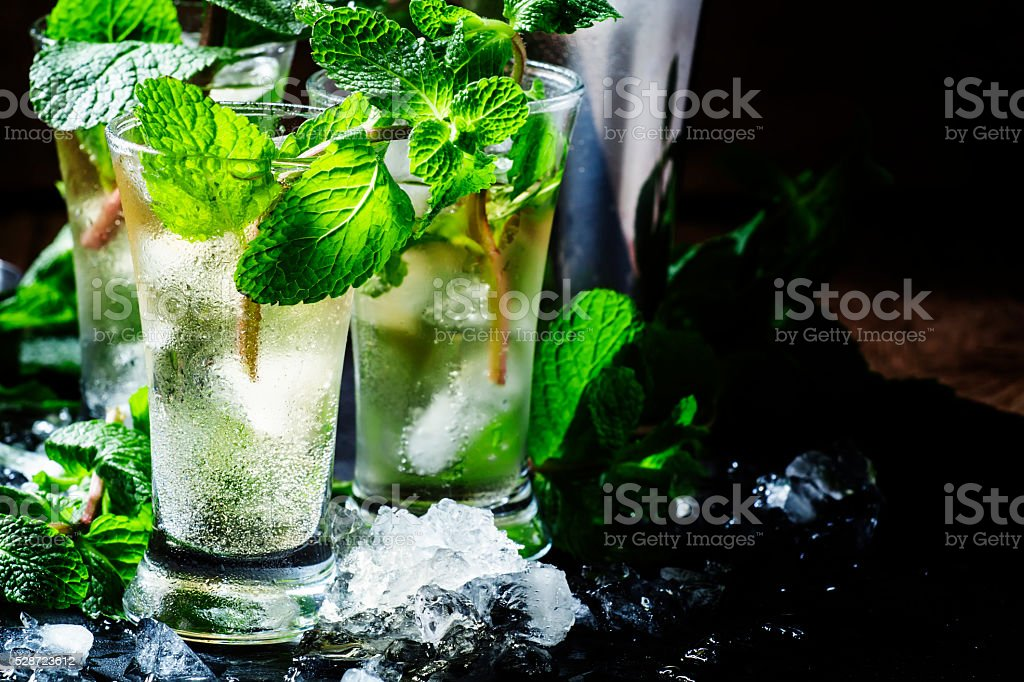 Green tea with ice, mint and white rum, dark background stock photo