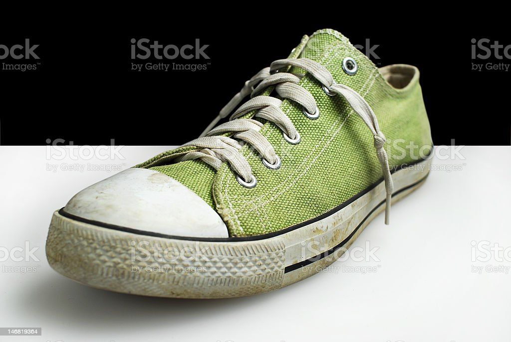 green teenager dirty sneaker black white background stock photo