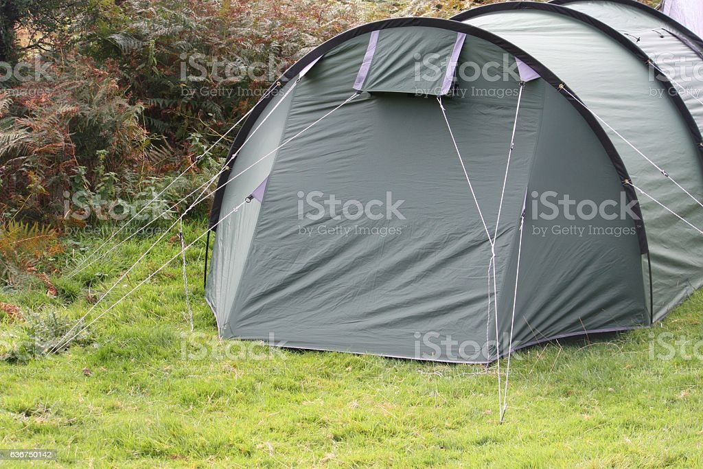 green tent pitched on grass stock photo